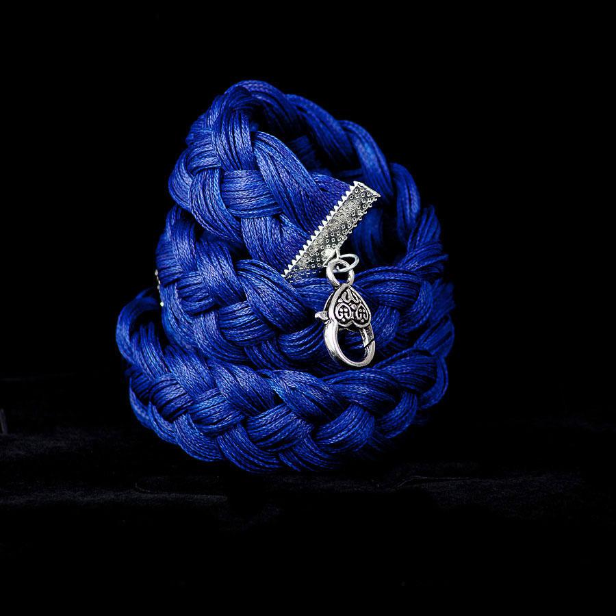Синий браслет на черном фоне